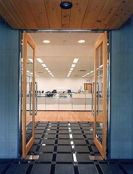 オフィスのエントランス。無機質なコンクリートパネルの外壁とナチュラルな木質が微妙にマッチしています。エントランス天井の節有りの木は無垢材を使用し、御影石の床がエントランスを主張しています。