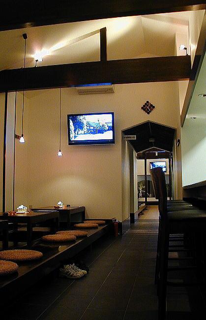 大人のくつろぎの世界 アプローチのドアが開くと、そこには驚くばかりの高い天井の第一の世界が広がります。この空間は、濃いめの床で仕上げられていてバーカウンターと小上がりで構成されています。お酒を飲み美味しいお料理を食べながらのお喋り。喫煙もできる大人のくつろぎの空間です。