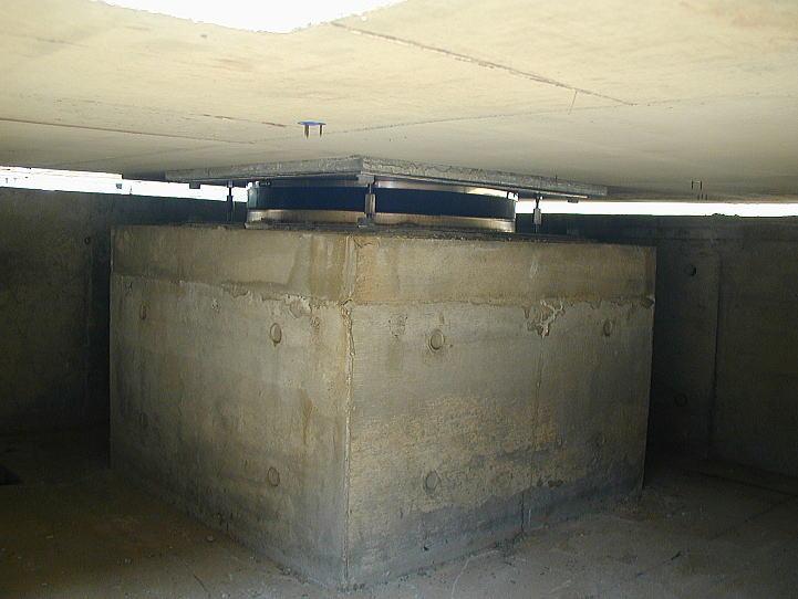 当該建物の免震装置。 鉄筋コンクリートの柱脚の上に免震装置を設置します。竣工までは、建物が容易に動かないように固定ボルトで固定していますが、竣工時に外して、フリーにします。 柱脚の上部10㎝程度を無収縮のコンクリートにして、髪1本の精度で水平を保ちます。