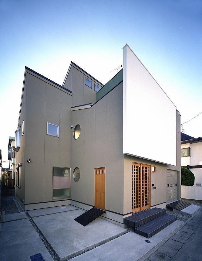 北側外観を駐車場側から観る。 建物と一体になった塀の格子戸を開けると、その奥に玄関が有ります。サイドの木戸は通用口です。 丸窓は、飾り窓をイメージし、和をモダンにアレンジしました。 全体を土壁の色でまとめ、一部に抹茶色をアクセントに配し、真っ白な漆喰調の壁が和を強調しています。