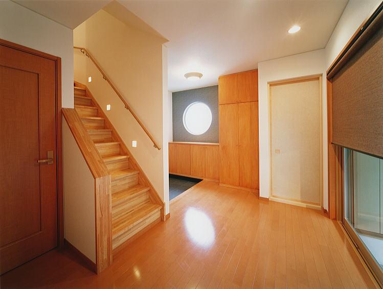 玄関ホール。 階段を上がると生活の中心、リビングへと繋がります。 中庭を望む大きな窓に簾調のロールブラインドをあしらい、和を醸し出しています。