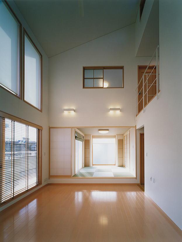 2階リビング。 2階、3階吹き抜けのリビング。南側に住宅が迫っているにもかかわらず、光が燦々と降り注ぎます。吹き抜け上部には、電動で開く欄間が有り、夏は、南から入った風が上部へ通り抜ける様にしました。 奥に見える部屋は茶の間です。