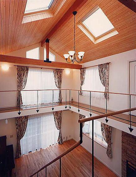 3階からリビングを見下ろす。リビング上部の3階には回廊が廻り、楽しさを演出すると共に構造の強化に役立っている。構造の梁を出し、木質の暖かさを感じさせている。