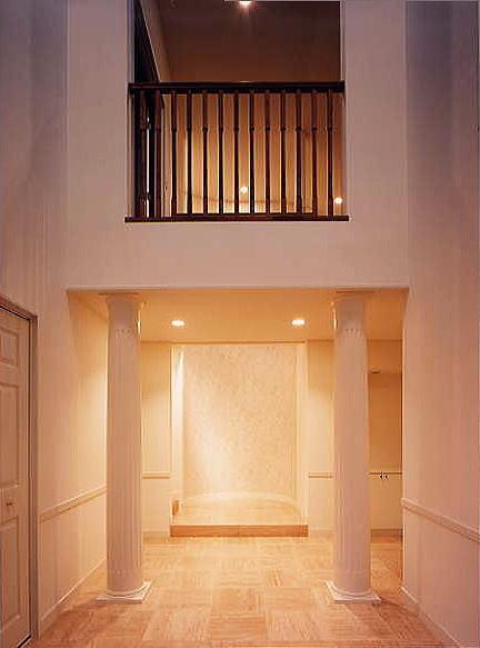 玄関ホールの吹き抜け空間を横切る橋を2本のエンタシスが支えています。また、正面の半円の壁はお客様を優しく出迎えます。