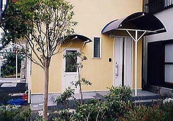 玄関庇はネイビーのアール屋根。軽快なお洒落を感じます。
