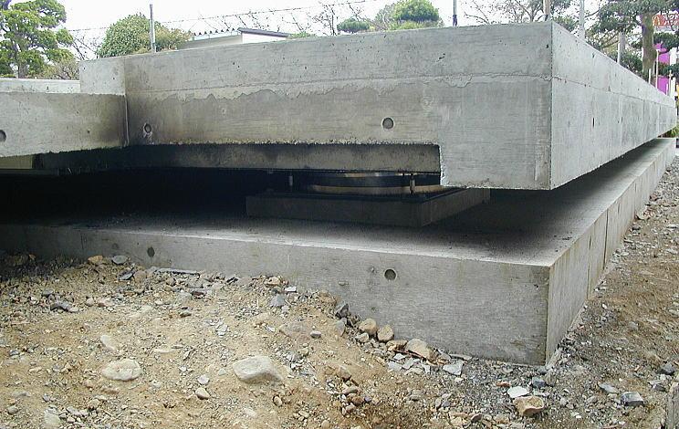 コンクリートデッキ下に設置された免震装置 デッキのコンクリートが固まり、型枠を外した状態を横から見ました。