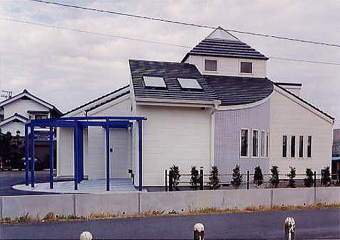 全景。目標物の無い広大な田園地域に建てられたので、四角錐のとんがり屋根が象徴的で地域の目印となるようにデザインされました。アプローチは半円でどの方向からもスロープで入れる様にしました。ブルーのパーゴラがお洒落です。
