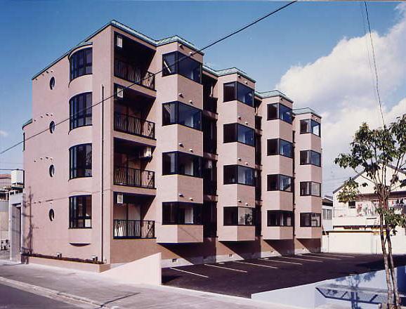 南面外観。賃貸マンションとは思えない、総タイル貼りの外壁と緑青銅板屋根。はね出した台形の部屋は光を十分取り込むことが出来ます。